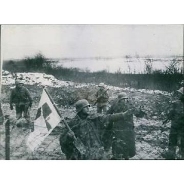 Bearing a red cross flag on shovel, two German soldiers surrender near Metz and
